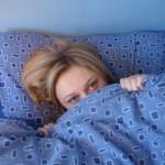 Girl in bed under duvet